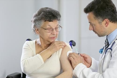 an elderly woman is preparing to receive a vaccine shot from a doctor