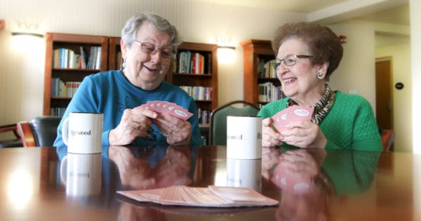Two senior women smile as they play cards together