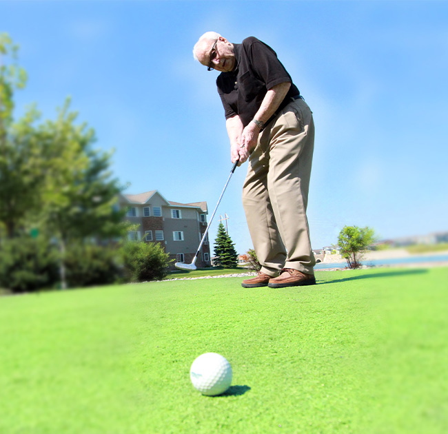 A senior man putts a golf ball on a bright, sunny golf course