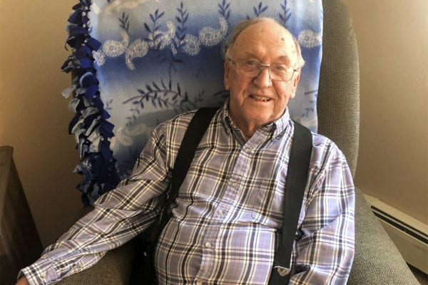 A portrait of Edgewood Healthcare resident Harold Weidler smiling at the camera as he sits in a green recliner