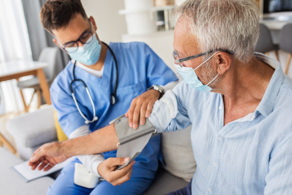 A young male doctor wearing a mask and scrubs takes a senior man's blood pressure during an in-home health visit.