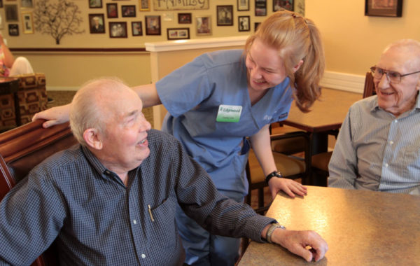 A young female nurse chats with two senior men in a dining room at Edgewood Healthcare